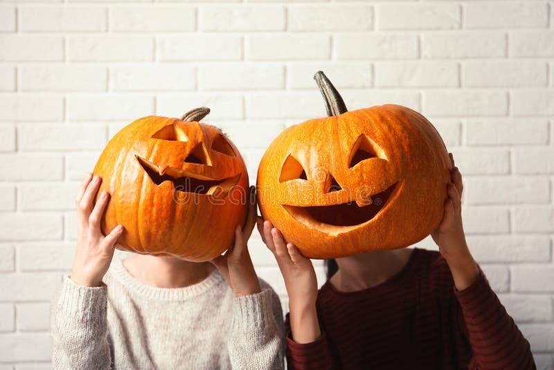 Women holding Halloween pumpkin head jack lanterns royalty free stock image