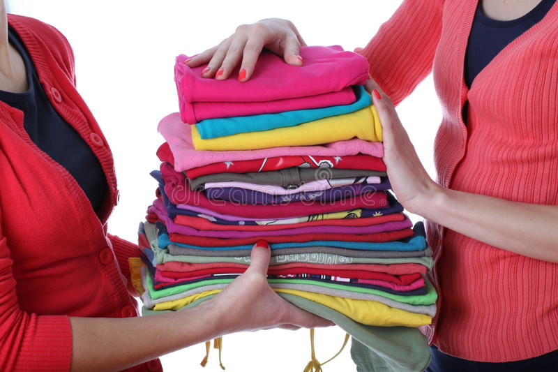 Women with ironed clothes. Women holding pile of ironed and colorful clothes stock images