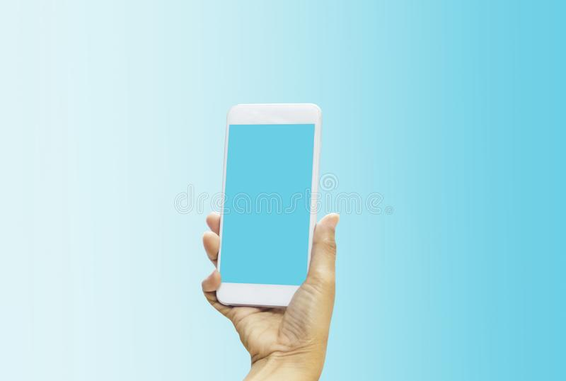 Women holding smartphone in hands with blue screen on bright blue-white pastel background. With concept of technology and royalty free stock images