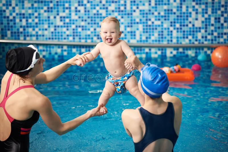 Women holding toddler lifting high up stretching exercising over water. Having fun in water. Activities in swimming pool royalty free stock photography