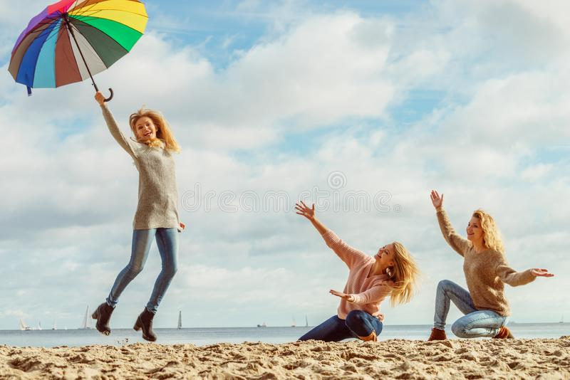 Women holding umbrella having fun with friends royalty free stock photos