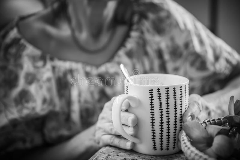 Women and hot drinks on hands. Backgrounds stock image