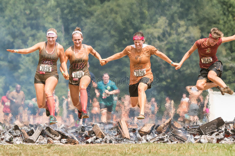 Women Hurdle Burning Logs Together In Extreme Obstacle Course Race. Conyers, GA, USA - August 22, 2015: A group of women holding hands jump together over burning stock photos