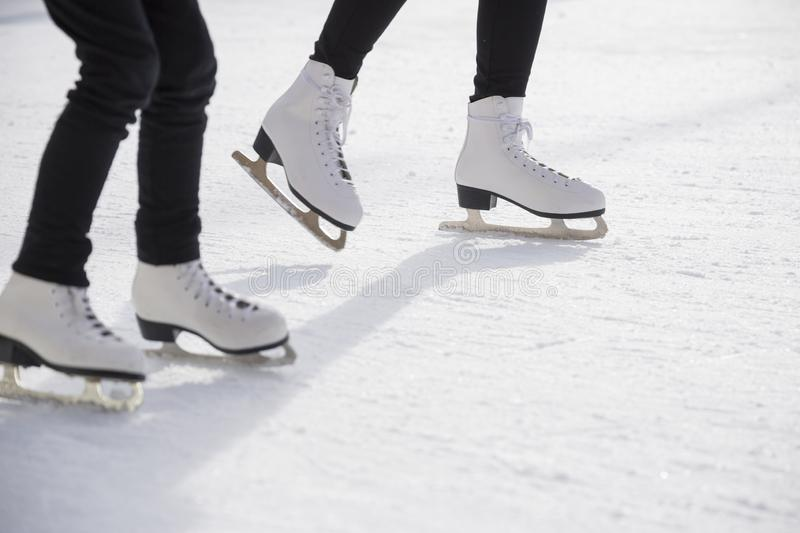 Women ice skating on ice rink. Young women ice skating on ice rink, close-up on skates royalty free stock photography