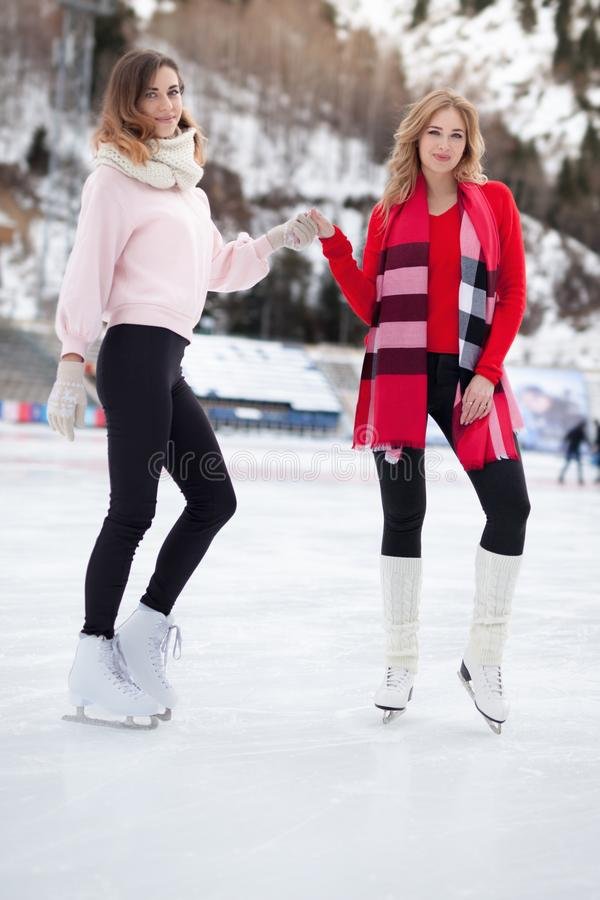 Women ice skating outdoor at ice rink royalty free stock photo