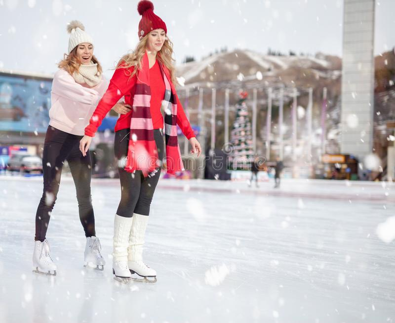 Women ice skating outdoor at ice rink royalty free stock photos
