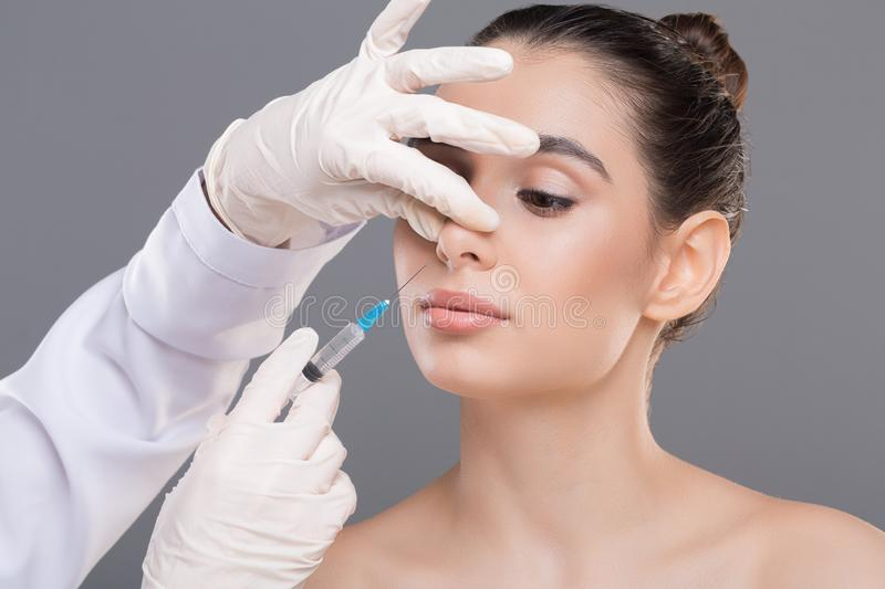 Women injected the cosmetic ingredients to the nose. Plastic surgery of nose. Doctor filling injection into female nose, alternative rhinoplasty stock images