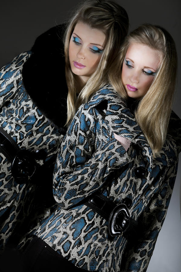 Women in jackets with snakeskin texture. Two young women in jackets with snakeskin texture royalty free stock photo