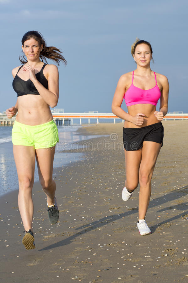 Women jogging on a beach stock photography