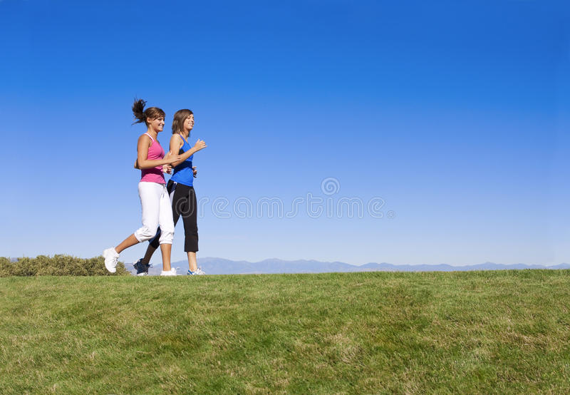Women Jogging & Fitness. Two attractive females jogging together with a beautiful, simple background royalty free stock images