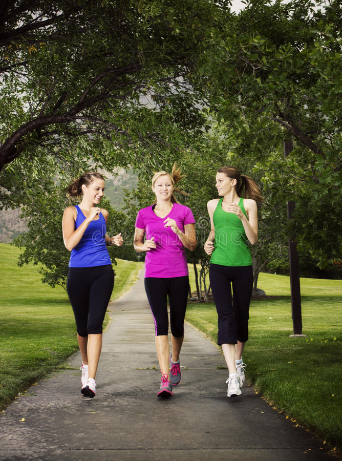 Women Jogging Together. Three healthy beautiful women enjoying a run together outdoors royalty free stock images
