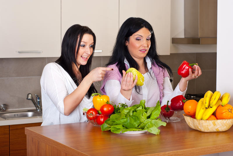 Women in kitchen choice peppers. Two women in kitchen having conversation and choice which pepper to use for salad royalty free stock photo