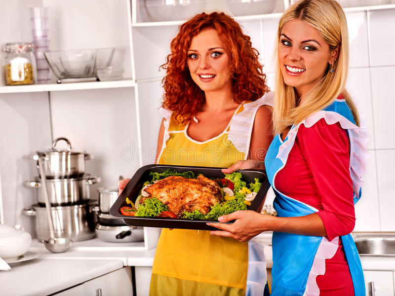 Women in kitchen is cooking roast meat food in oven. stock image