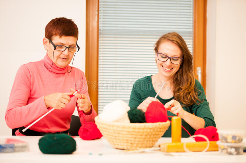 Women knitting with red wool. Eldery woman transfering her knowledge of knitting on a younger woman on handcraft workshop. royalty free stock photography