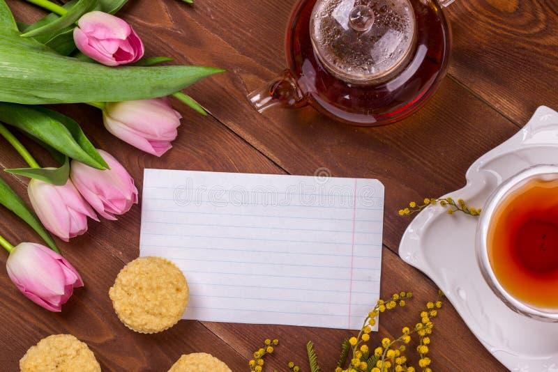 Women& x27; kort för s-daghälsning med tulpan, mimosan, te och muffin på brun träbakgrund royaltyfri bild