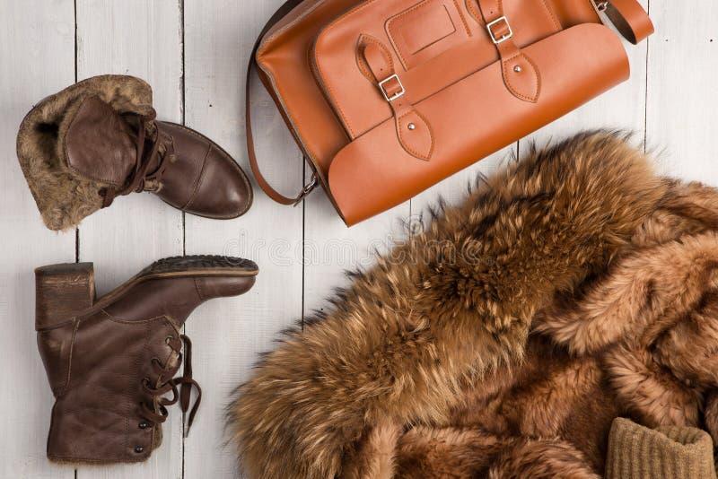 Women& x27; la s ha messo - una pelliccia, gli stivali caldi e una borsa fotografia stock