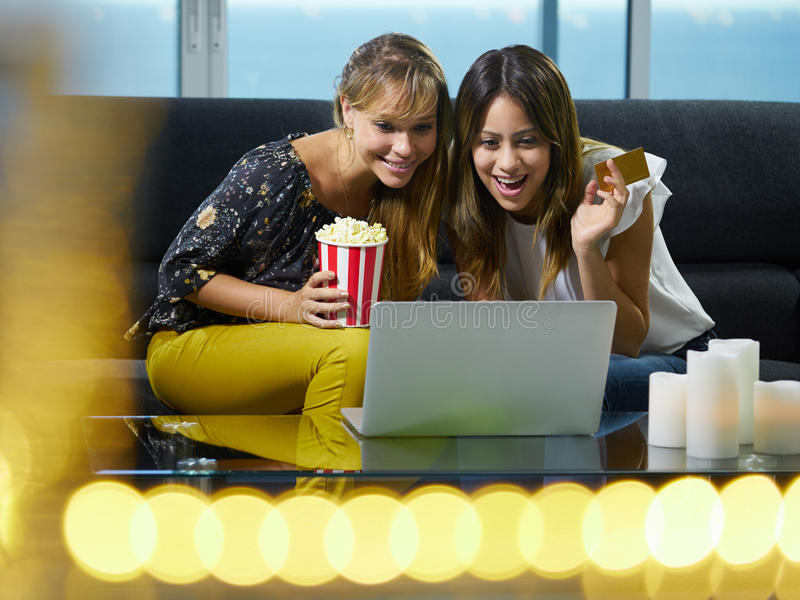 Women With Laptop PC Bidding At Online Auction. Two hispanic female friends sitting on sofa at home, looking at laptop computer and bidding online to buy an item stock photo