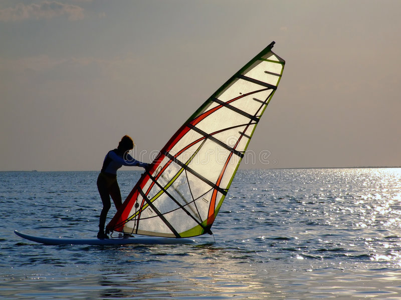 A women is learning windsurfin. G at the sunset 2 royalty free stock images