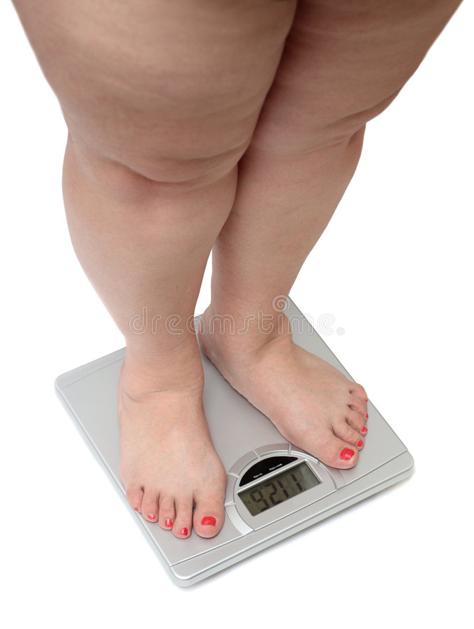 Women legs with overweight. Standing on bathroom scales stock photos