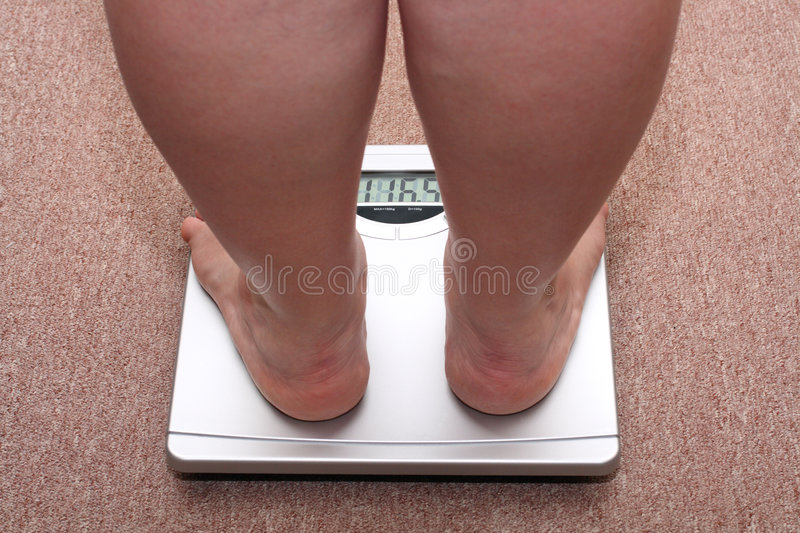 Women legs with overweight. Standing on bathroom scales royalty free stock photo