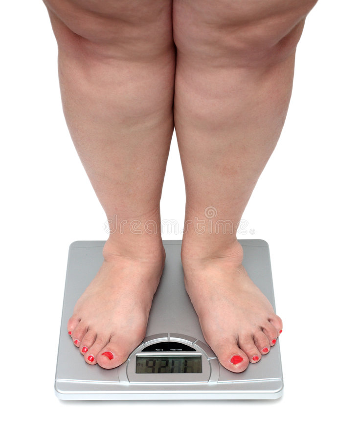Women legs with overweight. Standing on bathroom scales royalty free stock photos