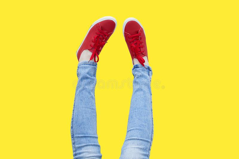 Women legs up in red sneakers. Yellow isolate royalty free stock photos