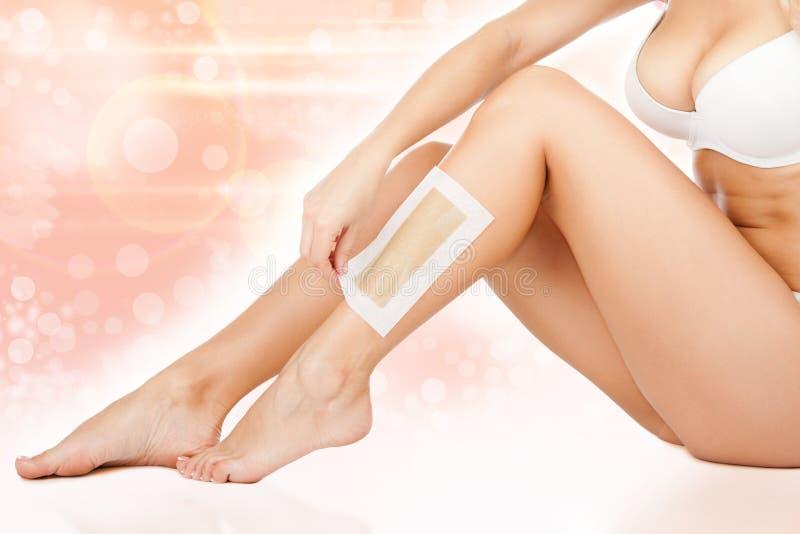 Women legs wax. Depilation epilation over flower background royalty free stock photo