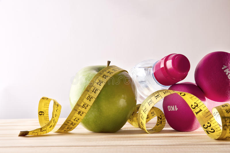 Women lifestyle health diet and sports isolated background front. Dumbbells with apple, mineral water bottle and tape measure on wood table and isolated stock photography