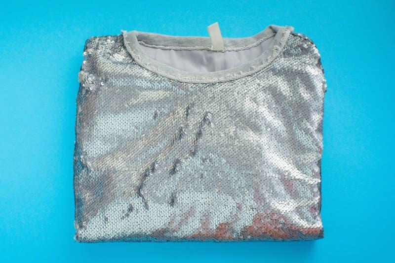 Women& x27; ligger den eleganta tröjan för s på ett blått mode för paljetter för dekor för textur för bästa sikt för bakgrund ski fotografering för bildbyråer