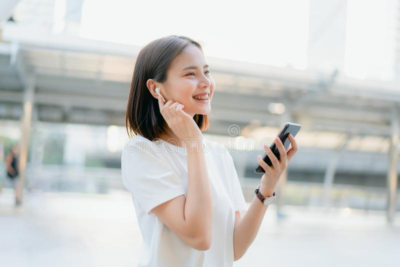 Women are listening to music from white headphones. And using hands touch to use various functions, happy mood stock images