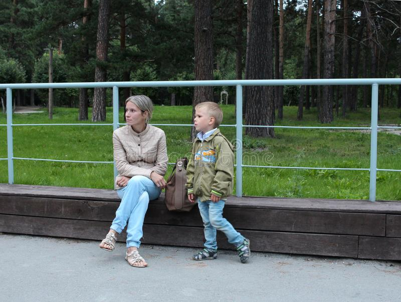 A woman with a small boy child walking in the Park sitting on a bench resting stock image
