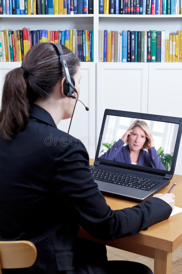 Women live video call counseling. Female psychologist in her office in front of her computer, talking to a extremely stressed middle aged women during a live stock photos