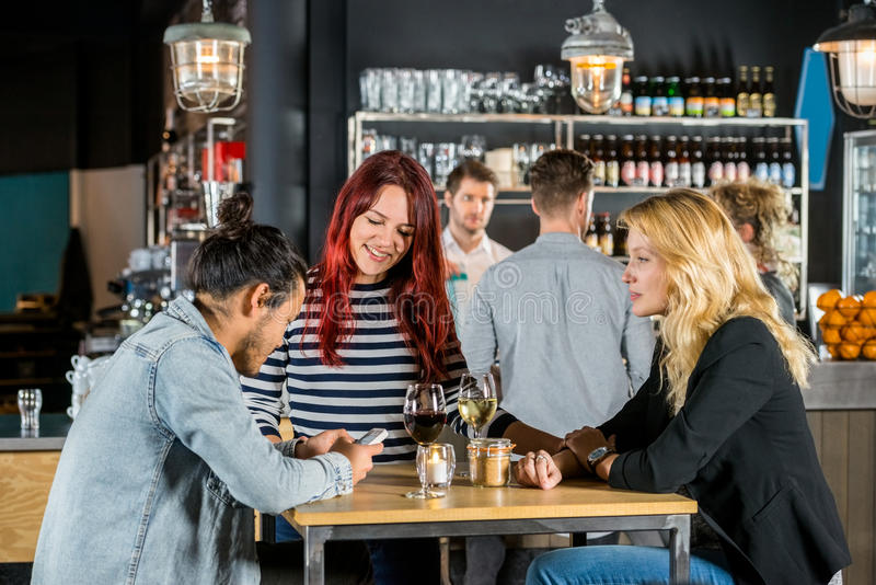 Women Looking At Friend Using Mobile Phone In Bar. Happy young women looking at male friend using mobile phone at table in bar stock photos