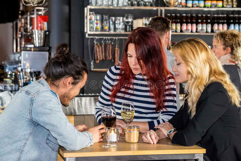 Women Looking At Friend Using Mobile Phone In Cafe. Young women looking at male friend using mobile phone at table in cafe royalty free stock photo
