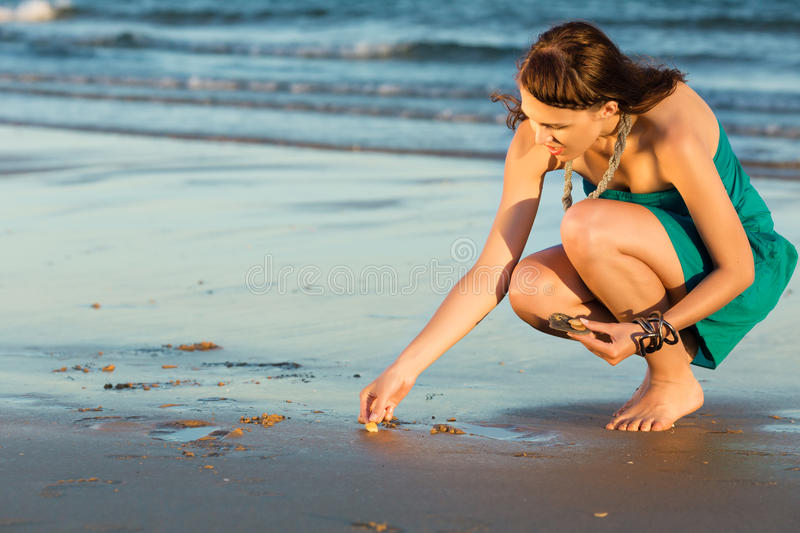 Women looking for sea shells in romantic sunset stock image