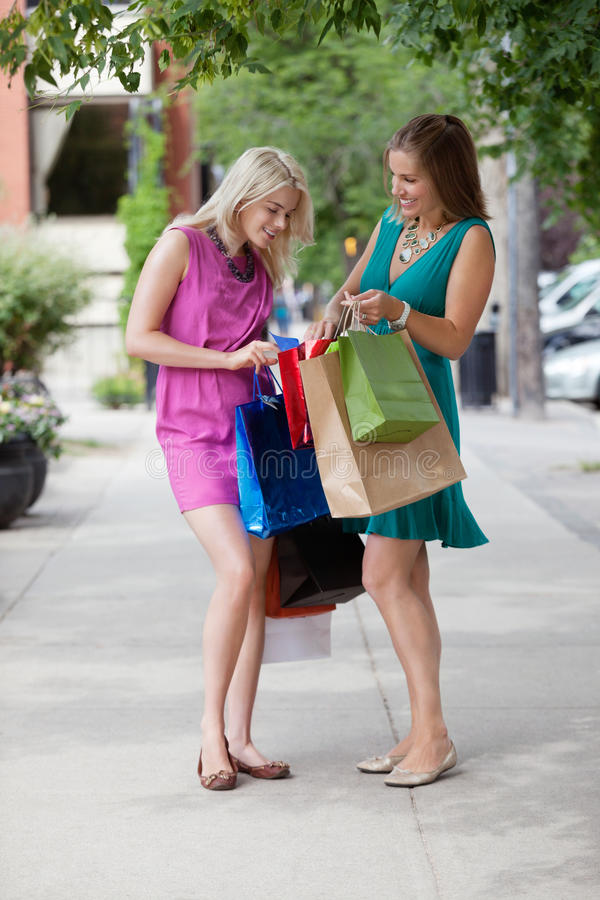 Women Looking Into Shopping Bags stock images
