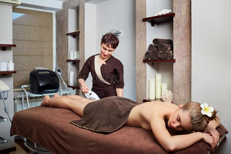 A woman lying down doing cryolipolysis treatment. royalty free stock images