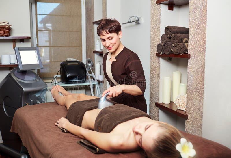 A woman lying down doing cryolipolysis treatment. stock photo