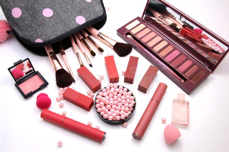 Women Make up Cosmetics bag and set of professional decorative, red lipsticks and brush makeup, perfume and sponge with pink pearl royalty free stock photo