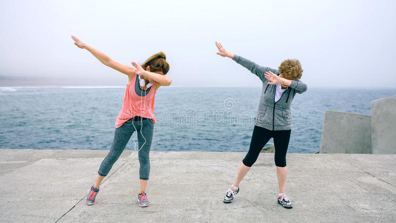 Women making dab dance outdoors. Senior and young women making dab dance outdoors by sea pier stock photography