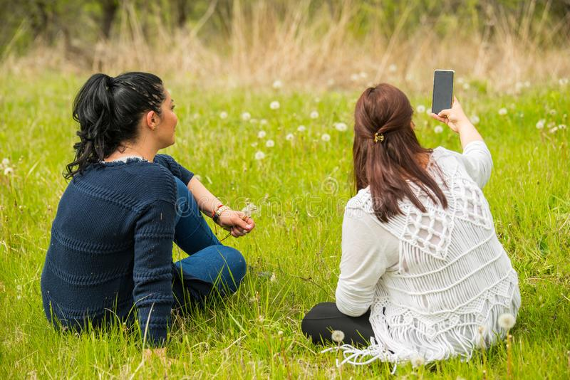 Women making photos with phone. Two friends women making photos in nature with smartphone royalty free stock photography