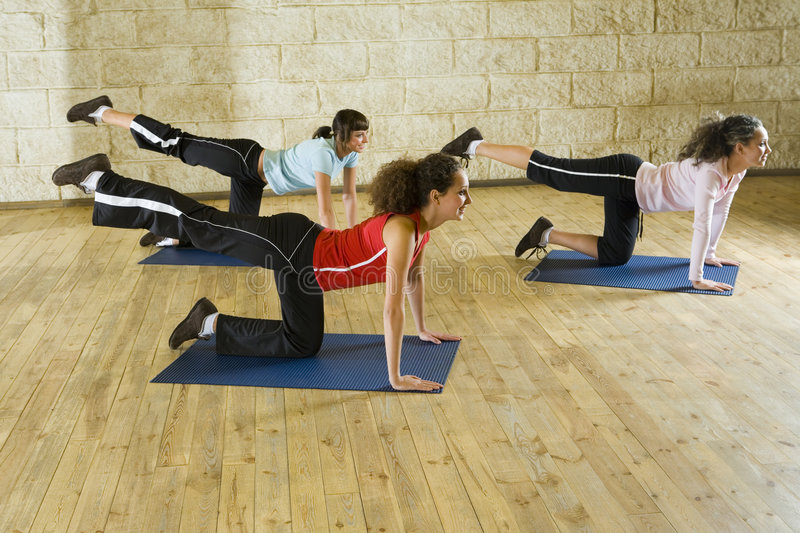 Women making stretching exercise on mat. A group of women making stretching exercise on yoga mat. Focus on the woman in red shirt. Front view royalty free stock photo