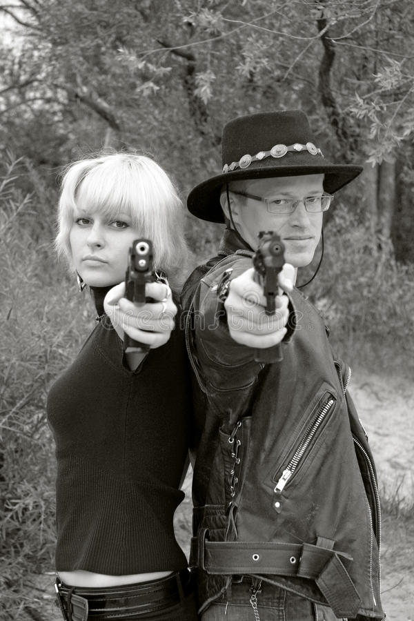 Women And Man Back-to-back Aiming Handguns Stock Images