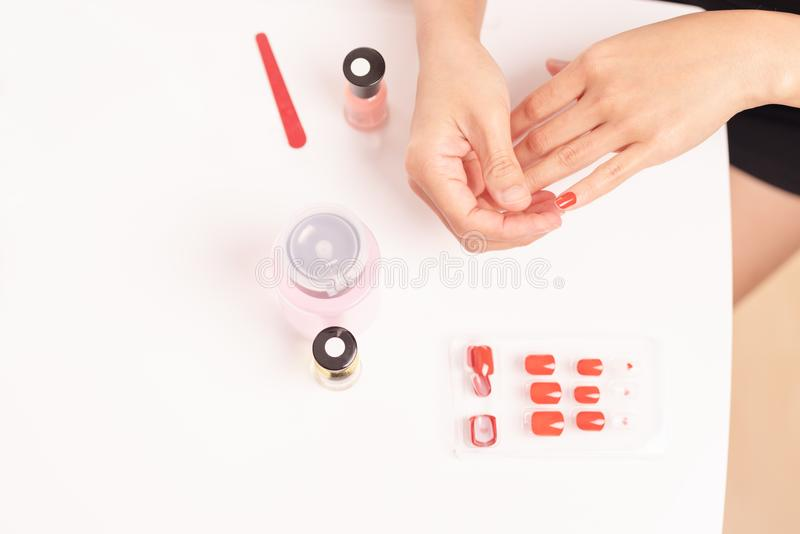 Women manicure and attaches a nail shape during the procedure of nail extensions with gel at home. Fashion and Beauty concept royalty free stock images