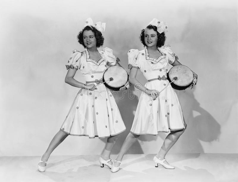 Women in matching outfits playing drums royalty free stock image