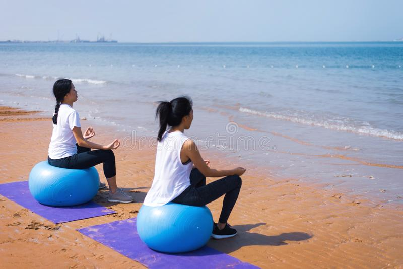 Women meditating on the beach. Women meditating with pilates ball on the beach meditate seaside yoga two friends together girlfriends asian female summer mat sit stock photos