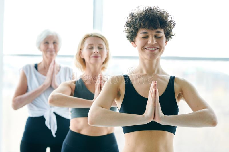 Women meditating. Happy young women keeping her hands put together by chest during yoga practice on background of two mature females royalty free stock photos