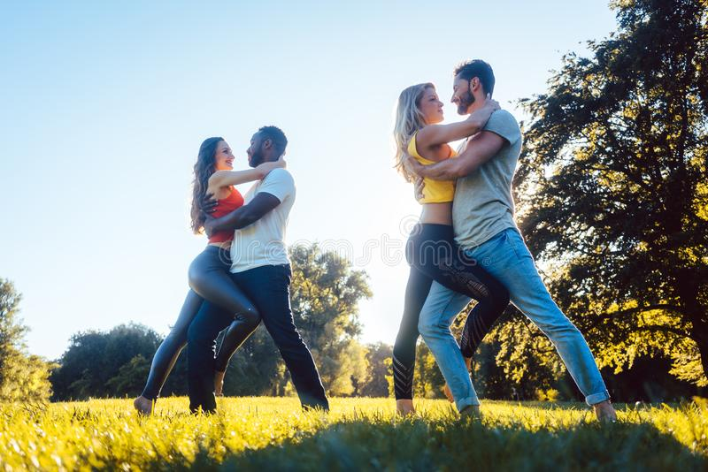 Women and men having fun dancing in the park. As couples stock photo