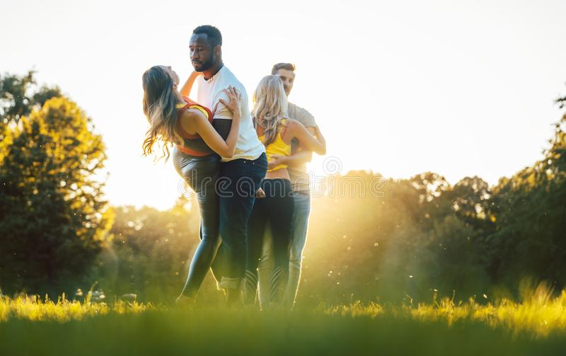 Women and men having fun dancing in the park. As couples royalty free stock image