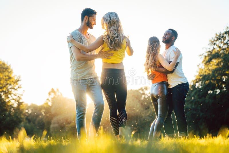 Women and men having fun dancing in the park. As couples stock photos